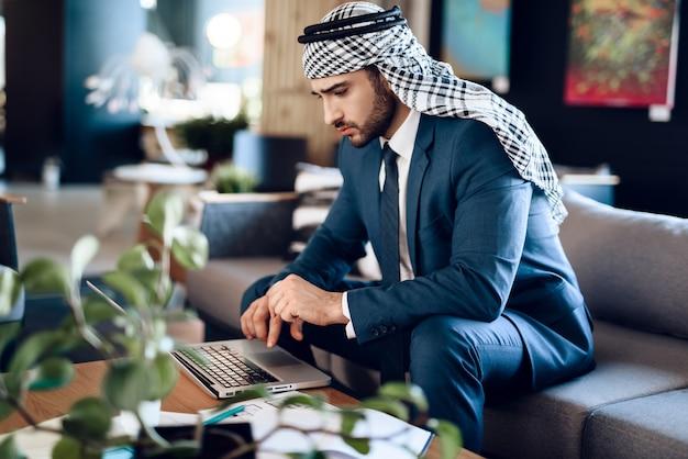 Homem de negócios árabe no lapton no sofá no quarto de hotel.