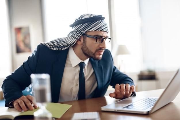 Homem de negócios árabe no terno que toma notas na tabela no escritório.