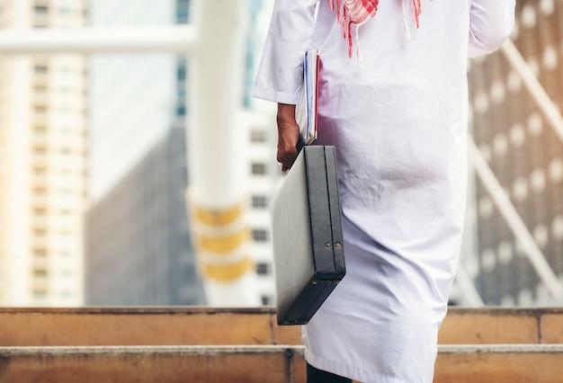 Homem de negócios árabe que guarda a pasta que anda acima das escadas na rotina do trabalho.