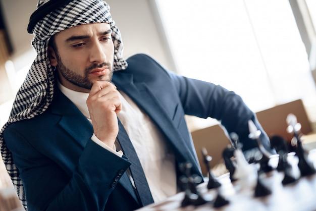 Homem de negócios árabe que joga a xadrez na tabela na sala de hotel.