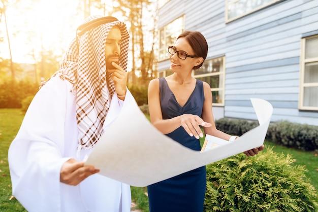Homem de negócios árabe que olha o mapa com plano de trabalho.