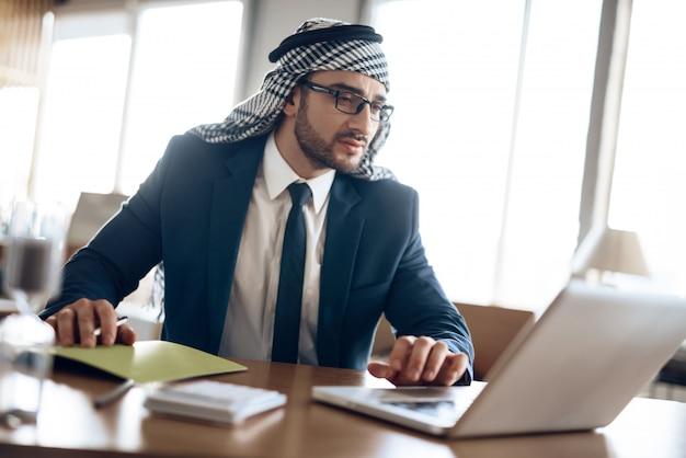 Homem de negócios árabe que toma notas na tabela na sala do escritório.