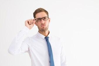 Homem de negócios arrogante ajustando os óculos e olhando para a câmera