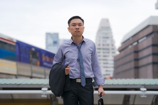 Homem de negócios asiático andando e segurando a mala com prédios de escritórios de negócios na cidade