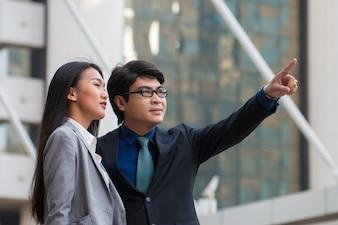 Homem de negócios asiático apontando algo e olhando para ele