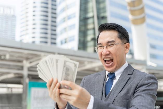 Homem de negócios asiático com cara feliz segurando notas de dólar americano no distrito comercial urbano