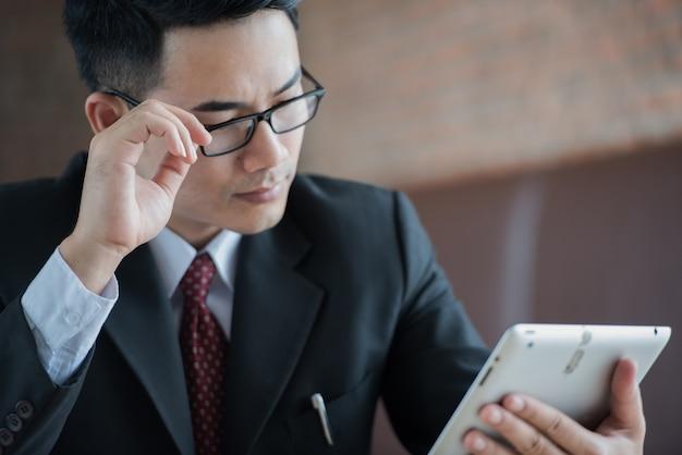 Homem de negócios asiático com os vidros que olham a informação na tabuleta na manhã.