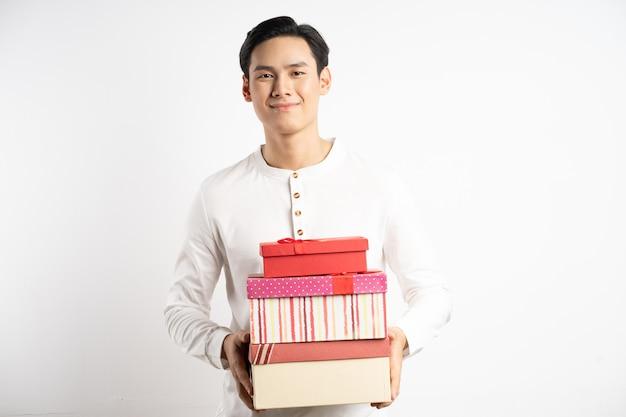 Homem de negócios asiático com três caixas de presente na mão