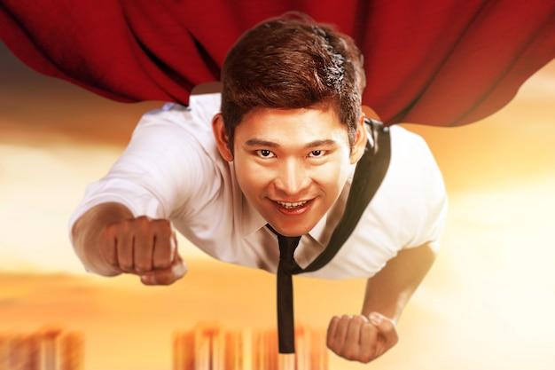Homem de negócios asiático com uma capa voando como um super-herói