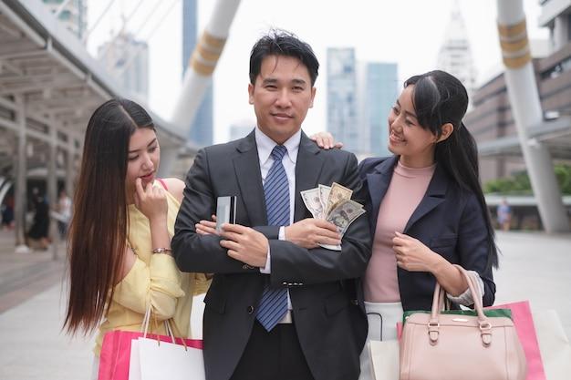 Homem de negócios asiático confiante e flertando segurando um cartão de crédito e um dólar em pé entre belas jovens mulheres asiáticas em meio urbano