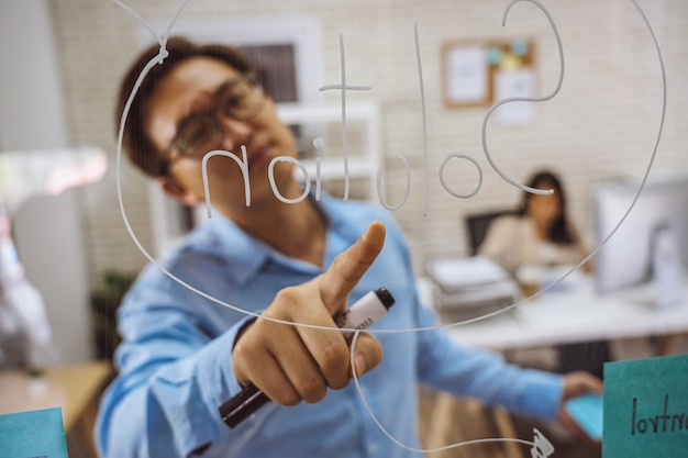 Homem de negócios asiático de close up apontando a solução com post-it na parede de vidro do escritório