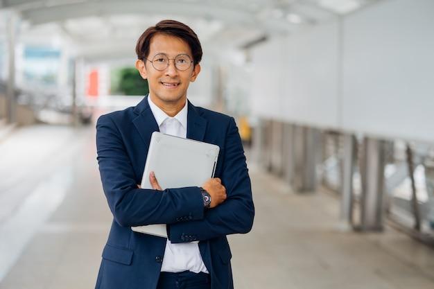 Homem de negócios asiático de retrato vestindo paletó andando vai trabalhar de manhã ao ar livre.