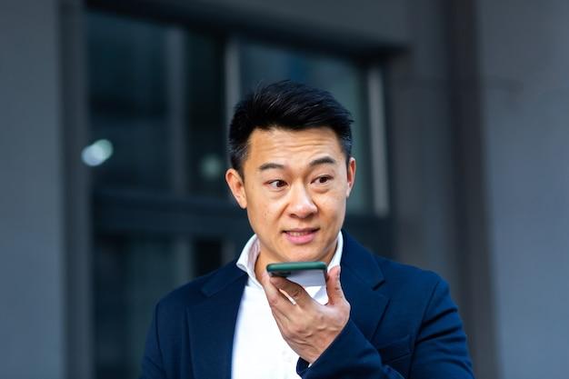 Homem de negócios asiático de sucesso irritado e sério explica as informações aos funcionários pelo telefone e fala perto do escritório, do lado de fora