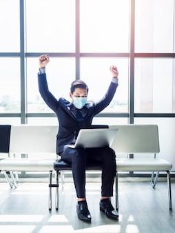 Homem de negócios asiático de terno usando máscara protetora ergueu as mãos feliz ao ver o monitor do laptop em seu colo