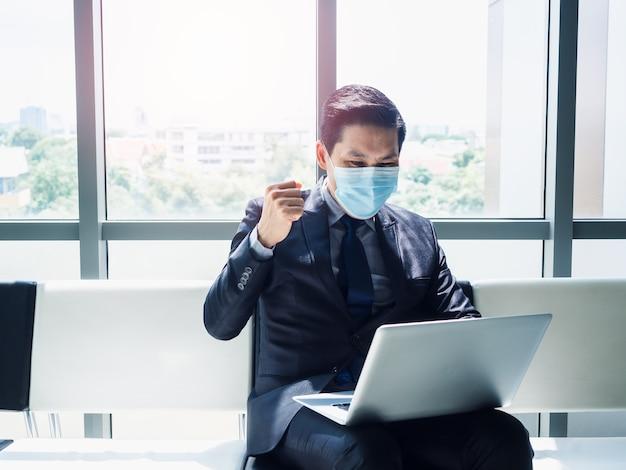 Homem de negócios asiático de terno usando máscara protetora levantou a mão com alegria e alegria ao ver um monitor de laptop em seu colo