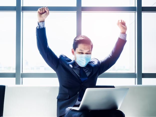 Homem de negócios asiático de terno usando máscara protetora levantou as mãos com alegria e alegria ao ver um monitor de laptop