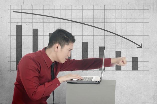 Homem de negócios asiático deprimido olhando relatório de impacto econômico global no laptop devido à pandemia de coronavírus