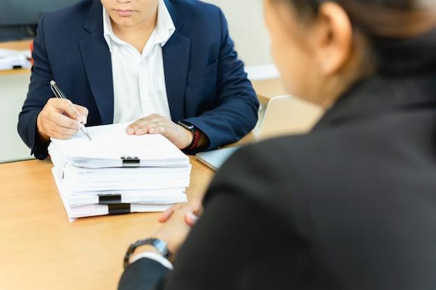 Homem de negócios asiático e seu trabalho de assinatura do original do secretário assistente no escritório.