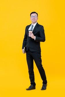 Homem de negócios asiático em terno formal, segurando a xícara de café e livro