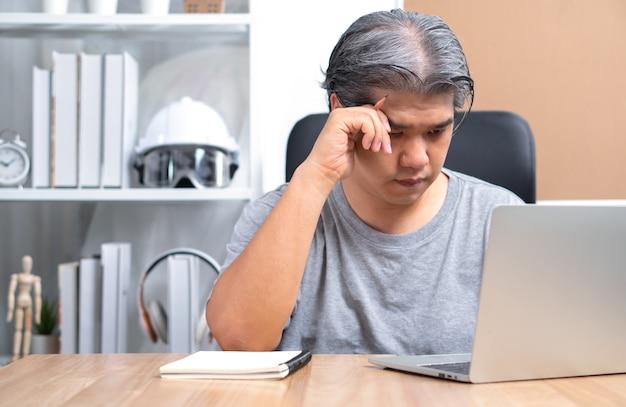 Homem de negócios asiático está trabalhando em casa para resolver problemas de negócios