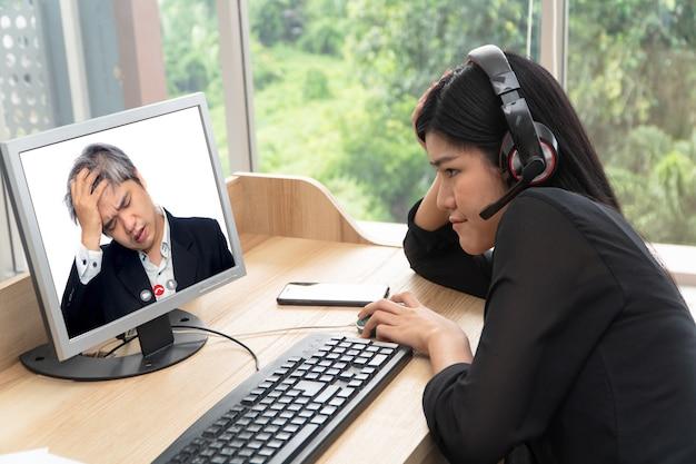 Homem de negócios asiático fazendo um vídeo ligue para o subordinado para falar sobre problemas de trabalho por meio da videoconferência.