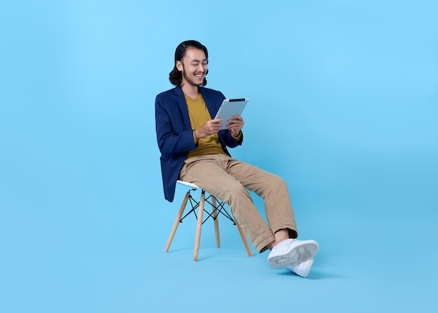 Homem de negócios asiático feliz sorrindo usando um tablet digital enquanto está sentado na cadeira em azul brilhante.