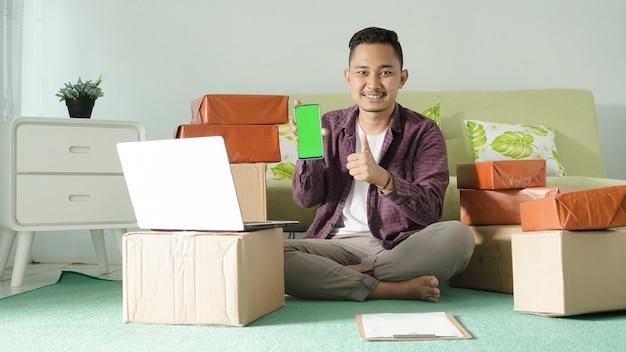 Homem de negócios asiático gesticulando na tela do smartphone na sala