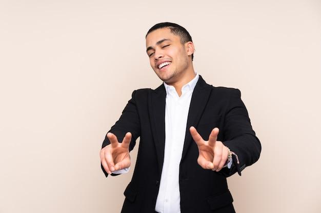 Homem de negócios asiático isolado em fundo bege sorrindo e mostrando sinal de vitória