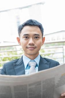 Homem de negócios asiático lendo jornal em cingapura
