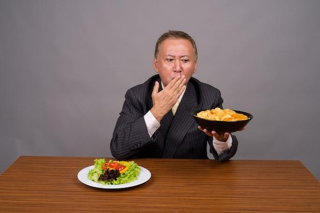 Homem de negócios asiático maduro sentado em uma mesa de madeira contra o cinza