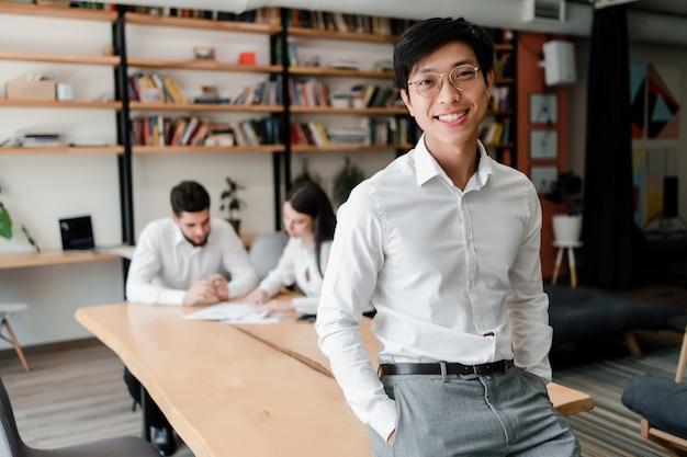 Homem de negócios asiático no escritório de óculos com colegas de trabalho no fundo