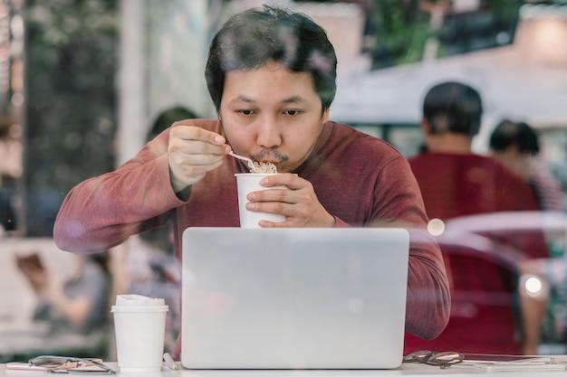 Homem de negócios asiático no terno ocasional que come o macarronete com ação urgente na hora do rush no des