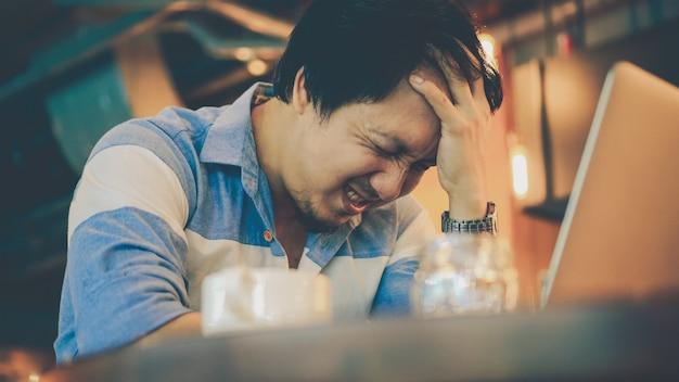 Homem de negócios asiático no terno ocasional que trabalha a ação disponivel da cabeça com emoção do esforço no co-wor