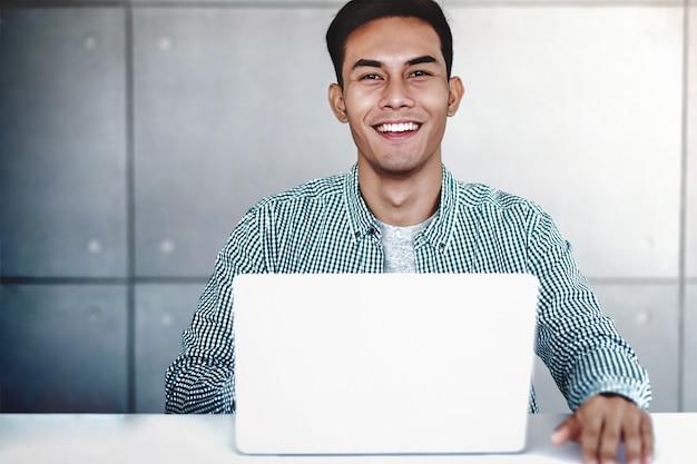 Homem de negócios asiático novo esperto working no portátil do computador no escritório. sorrindo e olhando para a câmera