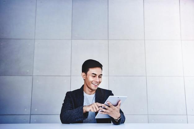 Homem de negócios asiático novo feliz que trabalha na tabuleta de digitas. sorrindo e sentado