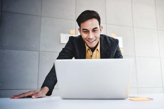Homem de negócios asiático novo feliz que trabalha no portátil do computador no escritório. de pé e sorrindo