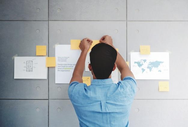 Homem de negócios asiático novo que trabalha na sala de reunião do escritório. homem, analisando, dados, planos, e, projeto