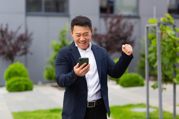 Homem de negócios asiático olhando para um celular e lendo notícias de ganhadores de loteria se alegra do lado de fora do escritório