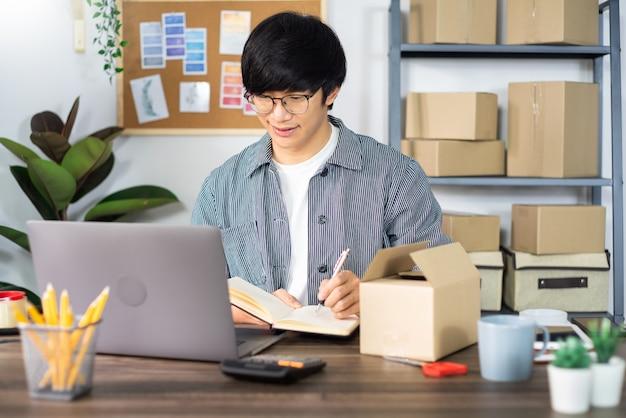 Homem de negócios asiático, preparando uma caixa de entrega