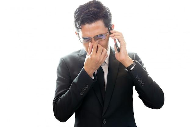Homem de negócios asiático que olha comprimido ao falar no telemóvel isolado.