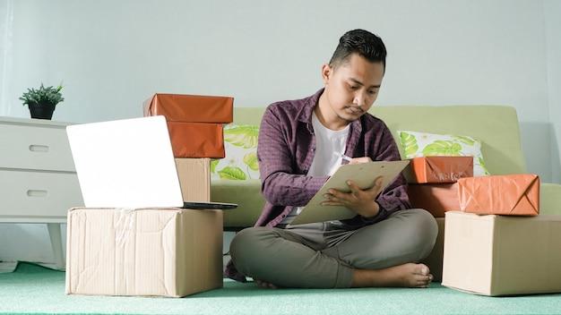 Homem de negócios asiático registrando produtos de vendas em casa
