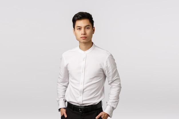 Homem de negócios asiático rico e bem-sucedido, de aparência séria e determinada, de camisa branca, calça preta, de mãos dadas nos bolsos, olhando a câmera, ouvindo o relatório dos funcionários sobre negócios,