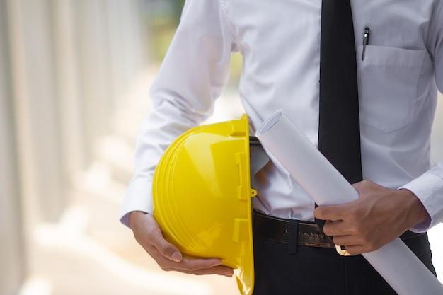 Homem de negócios asiático segurando capacete na construção do local