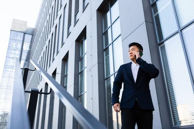 Homem de negócios asiático sério bem-sucedido falando ao telefone perto do centro de escritórios
