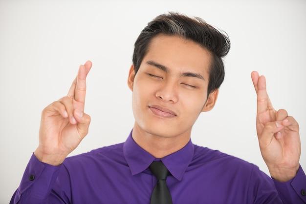 Homem de negócios asiático sonhador que mantém os dedos cruzados