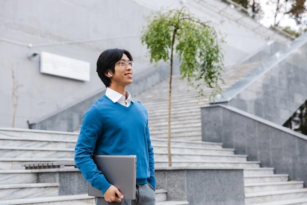 Homem de negócios asiático sorridente carregando um laptop ao ar livre, caminhando