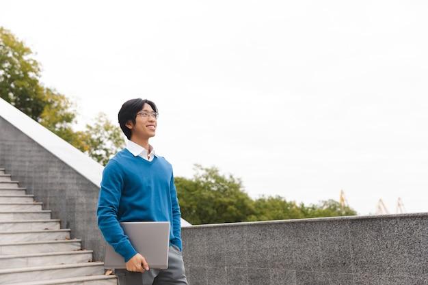 Homem de negócios asiático sorridente carregando um laptop ao ar livre