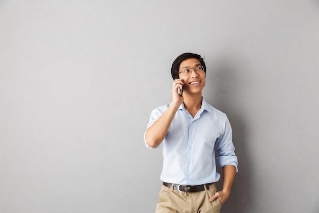 Homem de negócios asiático sorridente, isolado, falando no celular