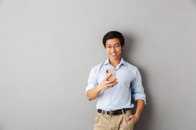 Homem de negócios asiático sorridente, isolado, usando telefone celular