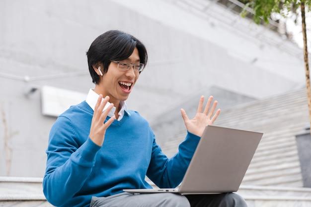 Homem de negócios asiático sorridente usando laptop ao ar livre